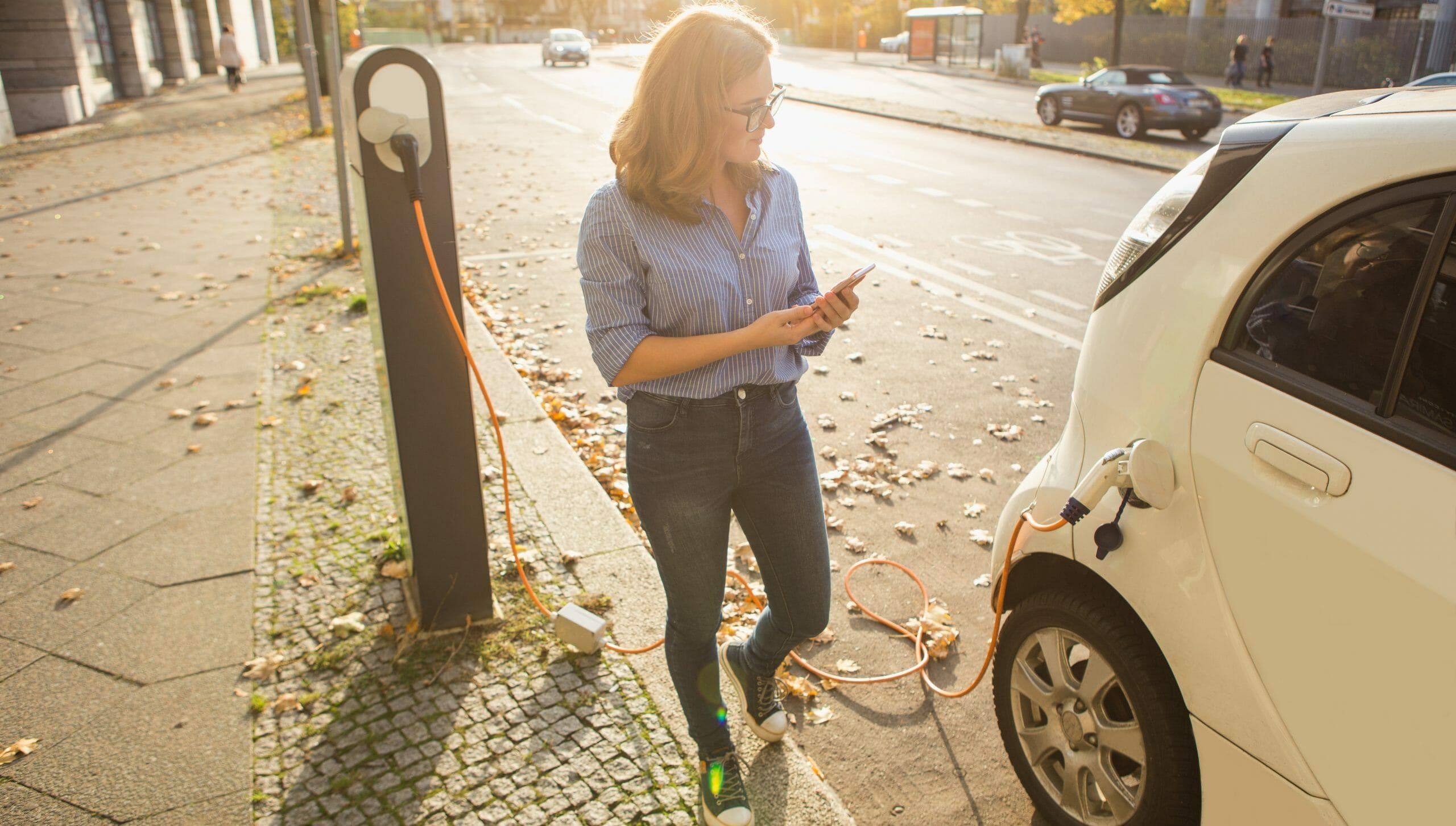 Een vrouw heeft haar elektrische auto op straat verbonden met een laadpaal en heeft haar telefoon in haar hand