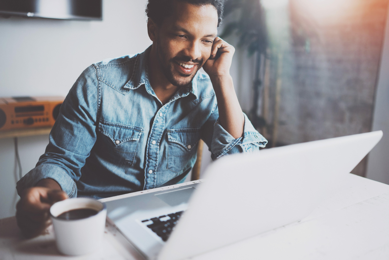 Man zit achter zijn iMac en drinkt een kopje koffie
